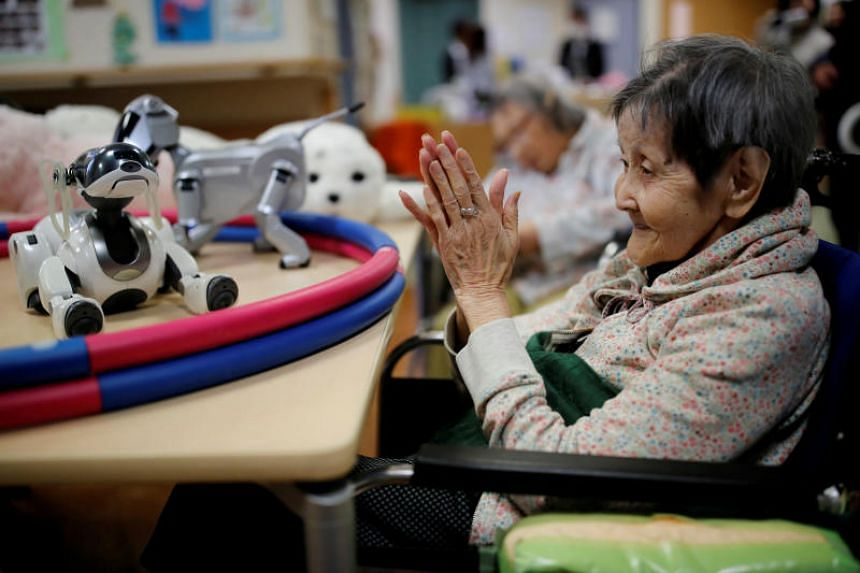 A resident claps to call Aibo, a pet dog robot at Shin-tomi nursing home in Tokyo, Japan, on Feb 2, 2018.