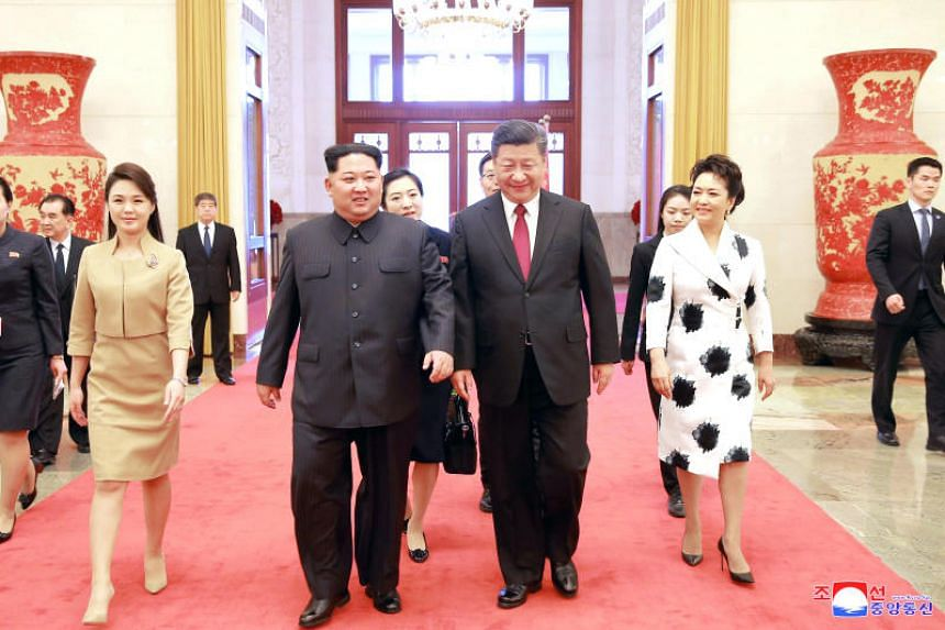 North Korean leader Kim Jong Un and his wife Ri Sol Ju walk with Chinese President Xi Jinping and his wife Peng Liyuan in this undated photo released by KCNA, in Pyongyang.
