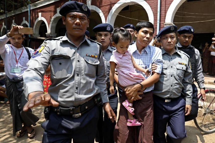 Detained Reuters journalist Kyaw Soe Oo (centre) is escorted by police as he holds his daughter during a break in the trial at the court in Yangon, Myanmar, on March 28, 2018.