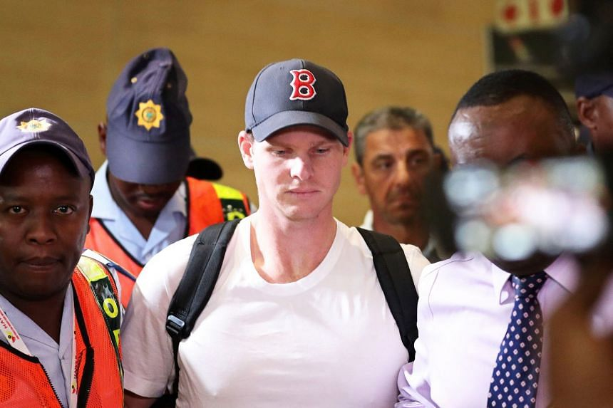 Steve Smith (centre) is escorted by police to the check-in counter for his flight to Australia.