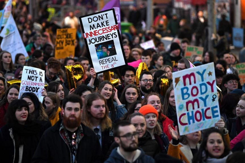 Demonstrators hold posters as they march for more liberal Irish abortion laws, in Dublin, on March 8, 2018.
