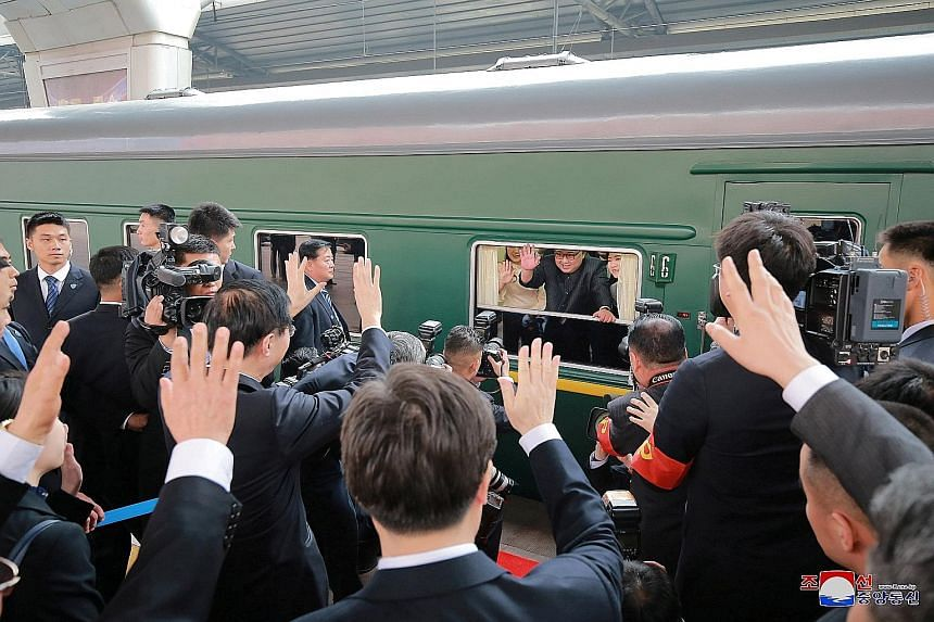 Mr Kim meeting Chinese officials inside a special train in an undisclosed location on Tuesday. The train he travelled in to Beijing was painted in drab green, and had 21 cars that were bulletproof. North Korean leader Kim Jong Un waving from his trai