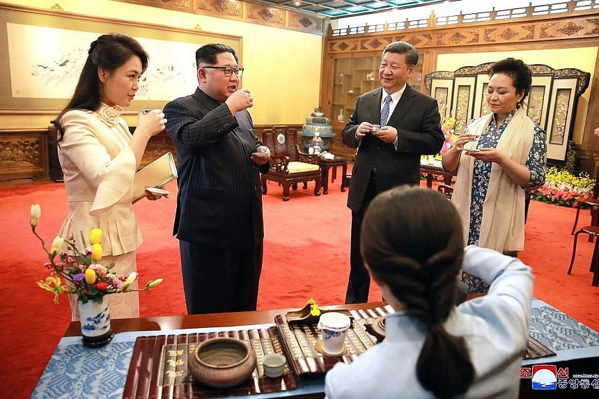 An undated photo released yesterday by the North Korean Central News Agency shows North Korean leader Kim Jong Un and his wife Ri Sol Ju (left) meeting Chinese President Xi Jinping and his wife Peng Liyuan at the Diaoyutai State Guesthouse in Beijing