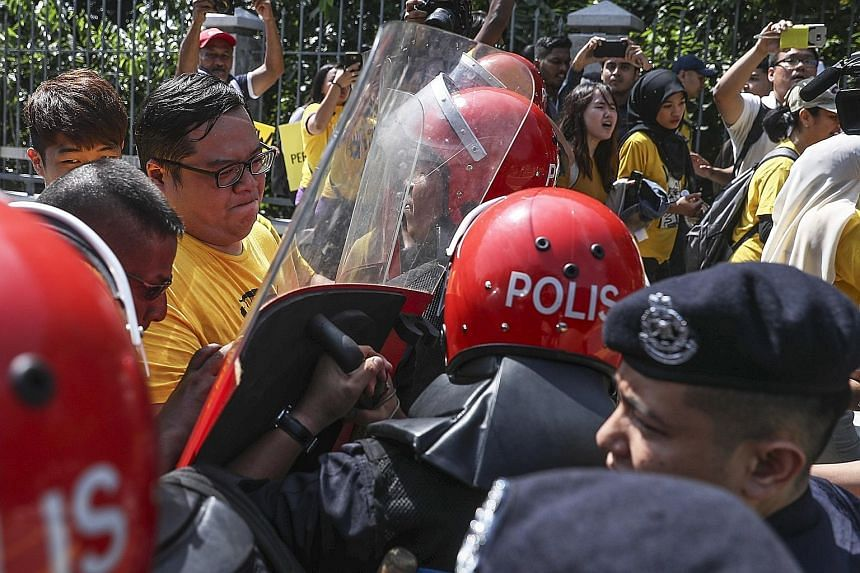 Prime Minister Najib Razak in the Malaysian Parliament yesterday, as protesters (right) scuffled with police during a rally against the tabling of the Election Commission's redelineation report. The crowd comprised opposition lawmakers and supporters