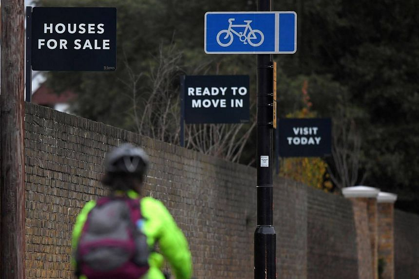 Property sale signs are seen outside of a group of newly built houses in west London on Nov 23, 2017.