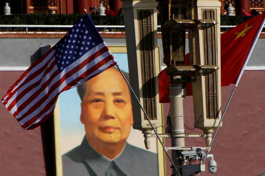 The flags of US and China flutter in front of a portrait of late Chinese Chairman Mao Zedong at the Tiananmen gate in Beijing on Nov 8, 2017.