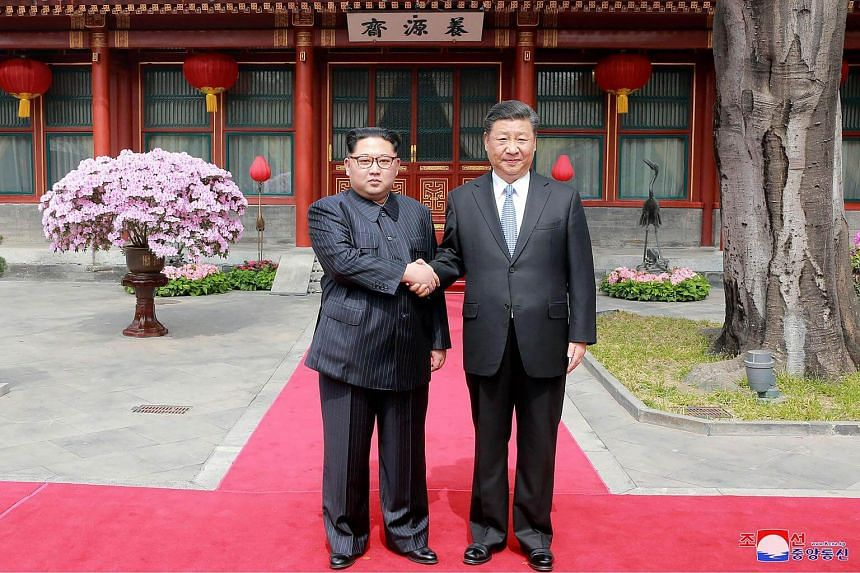 China's President Xi Jinping (right) shaking hands with North Korean leader Kim Jong Un in Beijing on March 27, 2018.