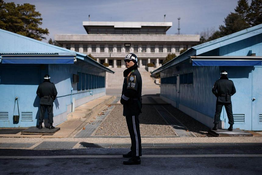 A South Korean soldier (center) stands guard before the military demarcation line and North Korea's Panmun Hall, in the truce village of Panmunjom, within the Demilitarized Zone dividing the two Koreas on Feb 21, 2018.