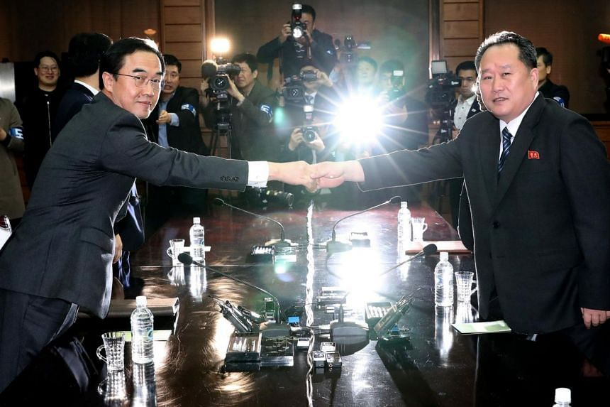 South Korean Unification Minister and chief delegate Cho Myoung Gyon (left) shakes hands with North Korea's chief delegate and Committee for Peaceful Reunification chairman Ri Son Gwon at the truce village of Panmunjom, North Korea, on March 29, 2018