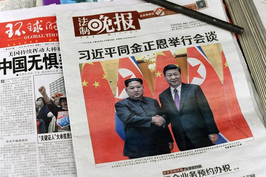 The front pages of Chinese evening newspapers, showing images of China's President Xi Jinping with North Korean leader Kim Jong Un, on display at a newspaper stand in Beijing on March 28, 2018.