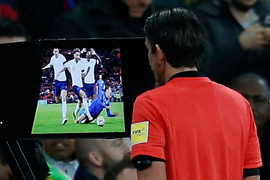 Left: England's James Tarkowski fouling Italy's Federico Chiesa at Wembley on Tuesday, resulting in a penalty following a (Video Assistant Referee) VAR review. Below: German referee Deniz Aytekin studying the VAR screen before reversing his decision