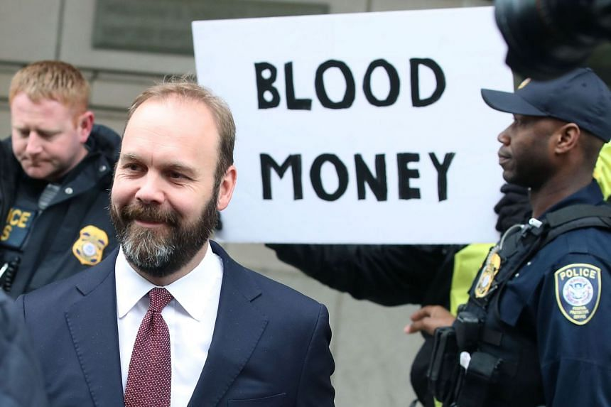 Rick Gates leaving court as a prostester holds up a sign, in February 2018 in Washington.