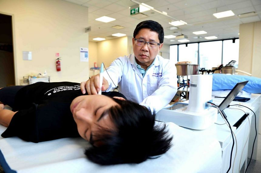 Associate professor Fabian Lim of exercise physiology at Nanyang Technological University's Lee Kong Chian School of Medicine tests for carotid-femoral pulse wave velocity, which is a non-invasive measure of arterial stiffness.