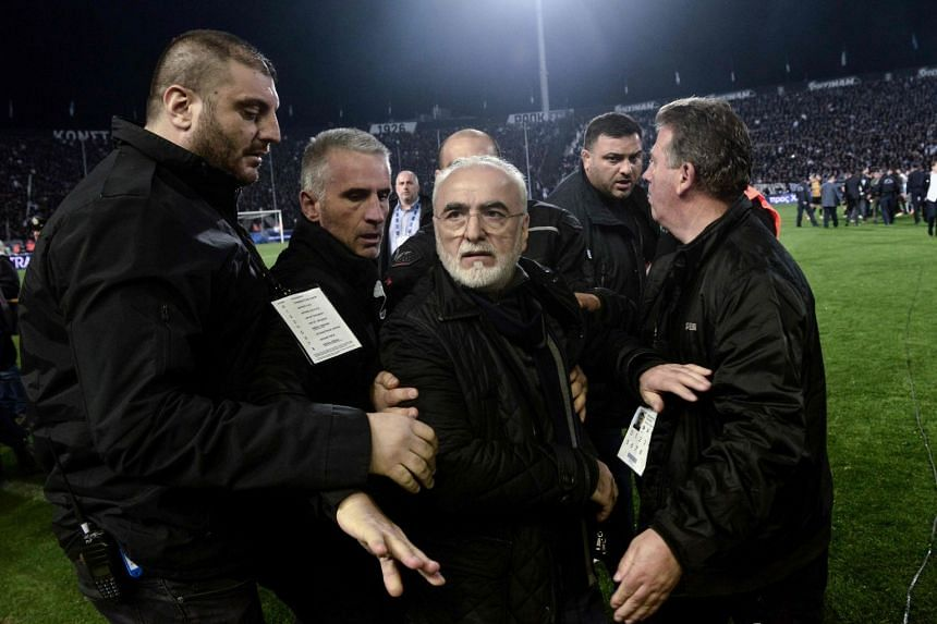 Paok's Greek-Russian president Ivan Savvidis (centre) is escorted out after taking to the pitch carrying a handgun in his waistband, after the referee refused a last minute goal during the Greek Superleague football match  on March 11, 2018.