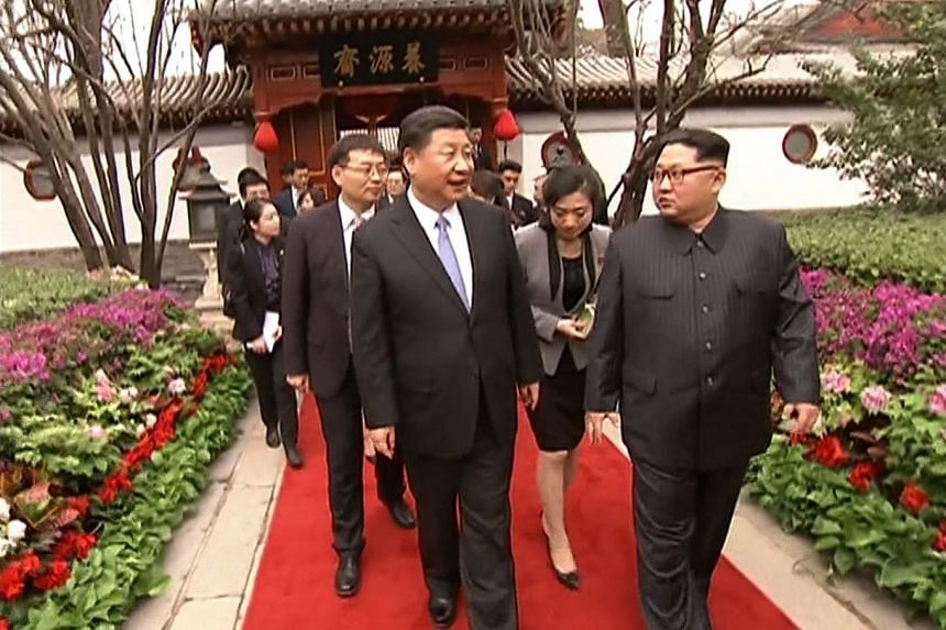Chinese President Xi Jinping (left) walking with North Korea's leader Kim Jong Un following their meeting in Beijing on March 28, 2018.
