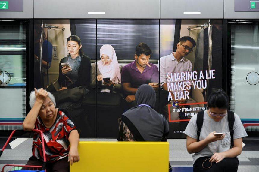 Commuters sit in front of an advertisement discouraging the dissemination of fake news, at a train station in Kuala Lumpur, Malaysia, on March 28, 2018.