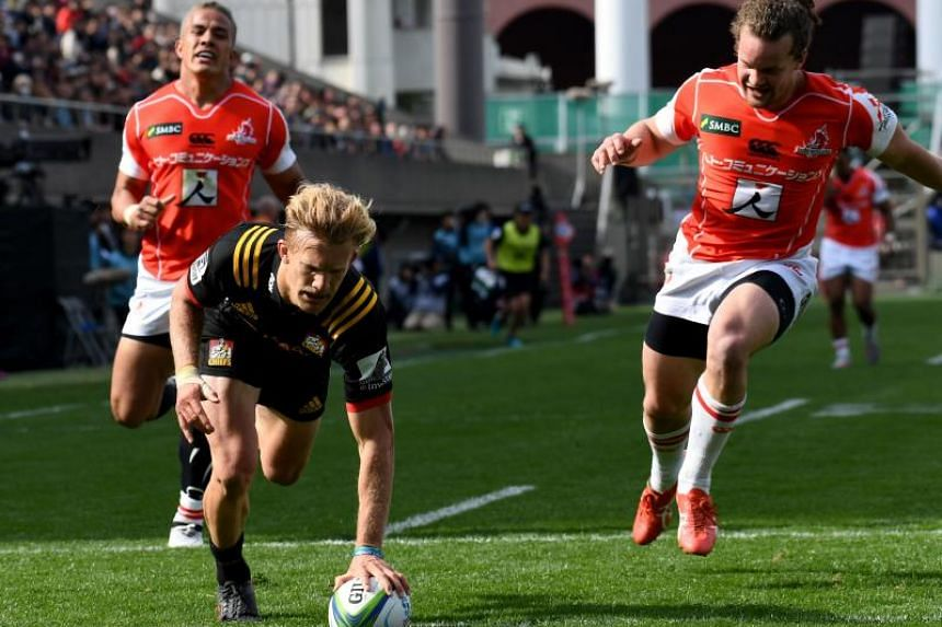 Damian McKenzie of New Zealand's Waikato Chiefs (centre) scores a try during the Super Rugby union match against Japan's Sunwolves at Prince Chichibu Memorial stadium in Tokyo on March 24, 2018.