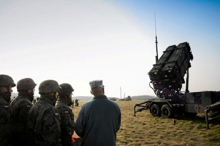 Polish and US soldiers look at a Patriot missile defence battery during joint exercises near Warsaw.
