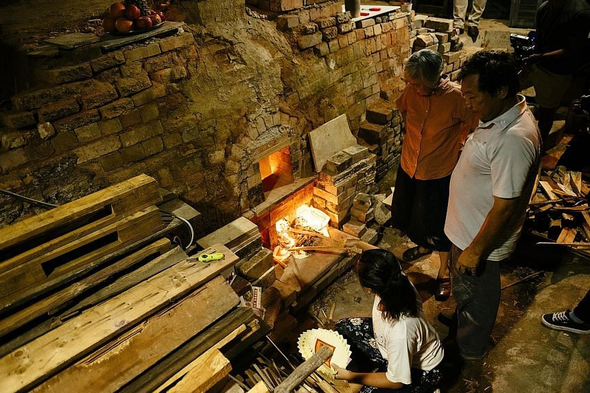 Ms Stella Tan, 27, stokes the fire at the last operational dragon kiln in Singapore, while family members Yulianti Tan, 59 (in pink), and Tan Teck Yoke, 61, look on. The kiln, located in the family-run Thow Kwang Pottery Jungle in Jalan Bahar, was bu