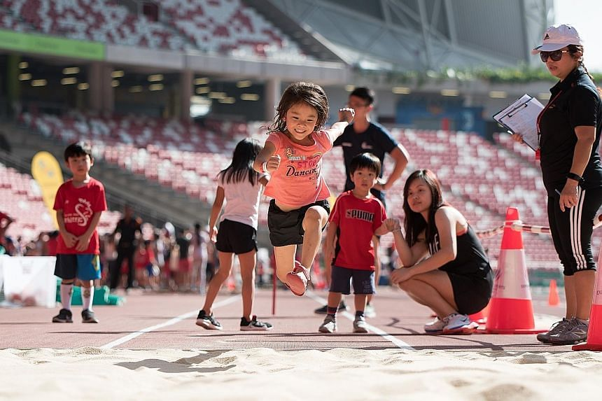A little girl putting her best foot forward at the long jump pit during the Singapore Athletics Association's athletics team challenge and tug of war last Saturday. The event was part of the 12-day open house at the National Stadium, which attracted