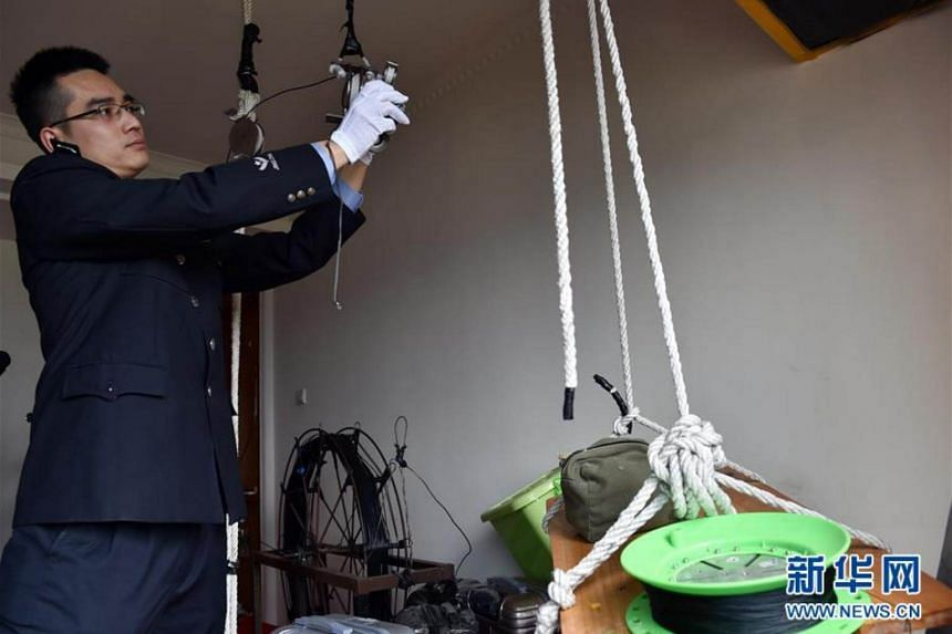 A police officer showing the tools used by the smuggling gang to set up a cable linking two high-rise apartments on opposite sides of the border and transported the goods with a power-driven winch.