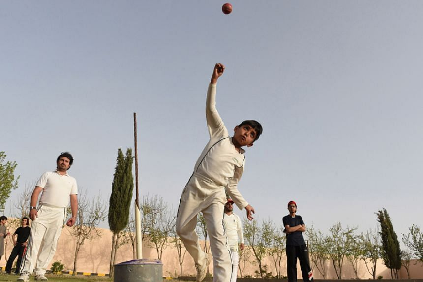 Pakistani child Eli Mikal Khan, 6, delivers a ball as his father Abdullah Khan (left, who is a local cricket coach and runs an academy, watches during a cricket bowling practice in Quetta on March 27, 2018.