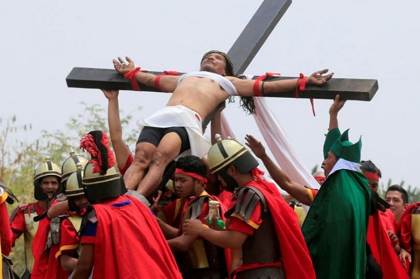 Ruben Enaje, 58, who is portraying Jesus Christ for the 32nd time, is nailed on a wooden cross during a Good Friday crucifixion re-enactment in Cutud village, Pampanga province, Philippines, on March 30, 2018.