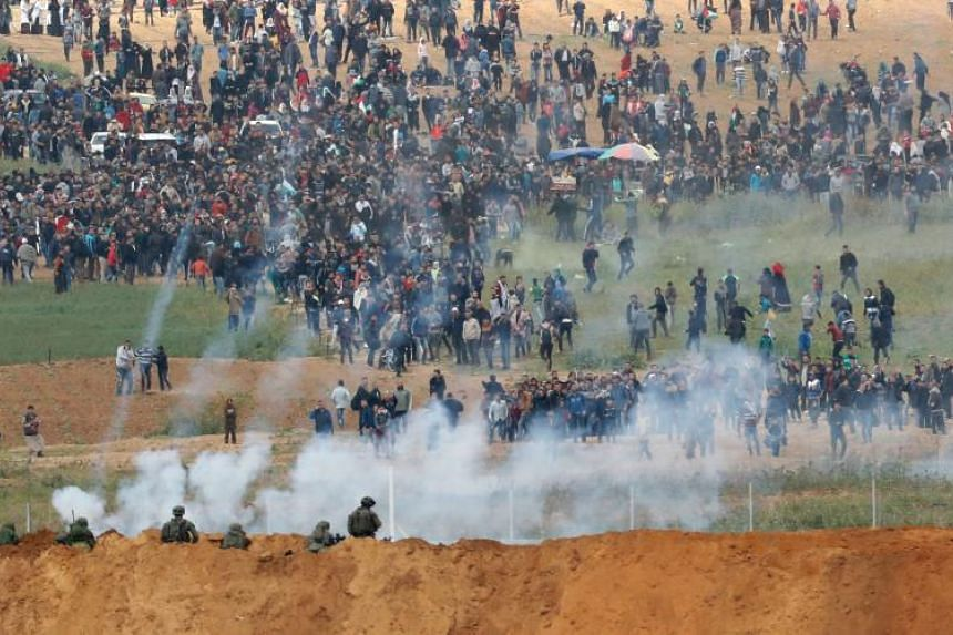 Tear gas grenades falling during a Palestinian tent city protest commemorating Land Day, with Israeli soldiers seen below in the foreground, near the border from the Gaza strip on March 30, 2018.