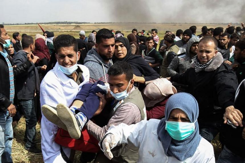 An injured Palestinian woman is carried by protesters as they run for cover during clashes with Israeli security forces following a demonstration commemorating Land Day near the border with Israel, in the southern Gaza Strip on March 30, 2018.