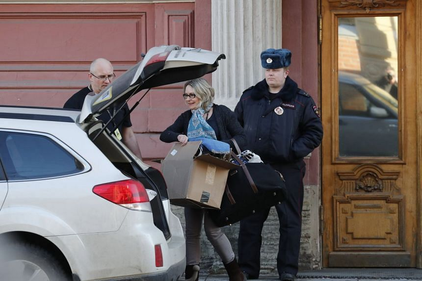 A woman carries bags as she leaves the US Consulate General in St Petersburg.