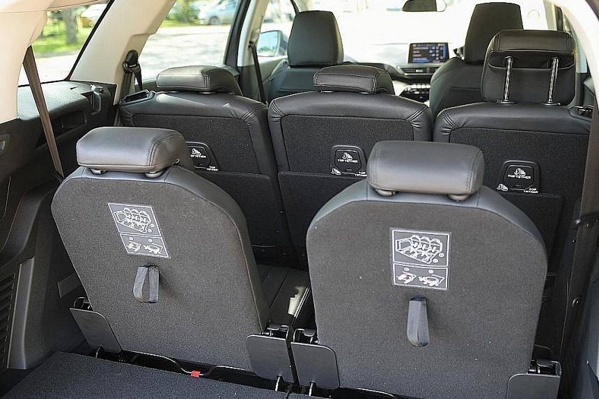 Peugeot's 5008 1.2 (left) has many amenities, including wireless phone charging, electric parking brakes and infotainment touchscreen with plenty of connectivity (above), like the 3008 (right). And it carries two more passengers (below) than the 3008