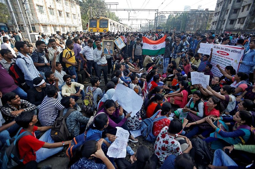 People occupying railway tracks as they block train services during a protest demanding recruitment into the state-run railway services in Mumbai, India, earlier this month.