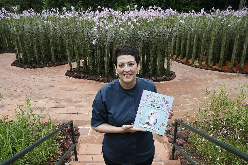 Ms Linda Locke, the great grandniece of Agnes Joaquim, at the Botanic Gardens with her book titled Agnes And Her Amazing Orchid. Behind her are displays of the Vanda Miss Joaquim, originally cross-bred by the horticulturist in the 19th century.