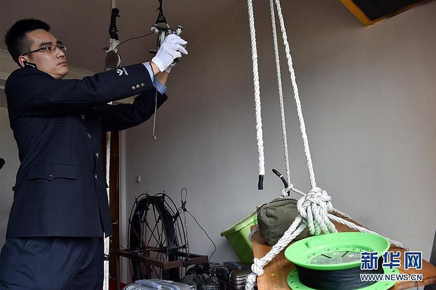 A police officer showing the tools used by a smuggling gang to set up a cable linking two high-rise apartments on opposite sides of the mainland-Hong Kong border. A power-driven winch was then used to transport cellphones across the cable link. A sma