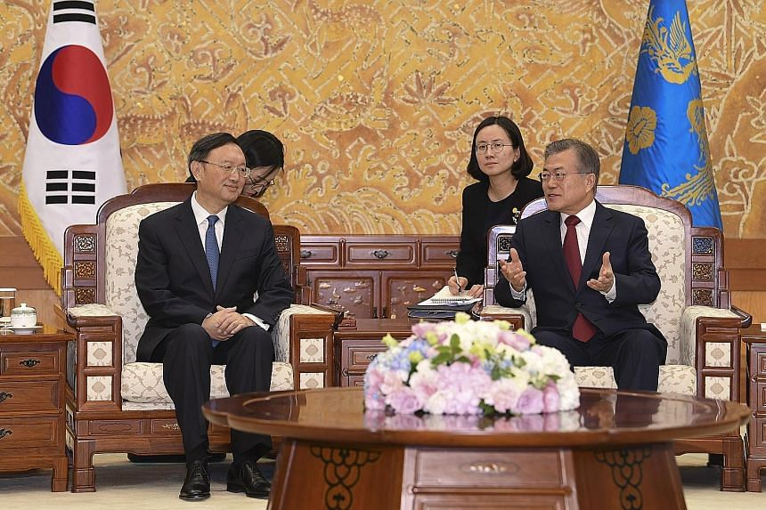 South Korea's President Moon Jae In (right) with top China diplomat Yang Jiechi in Seoul yesterday.