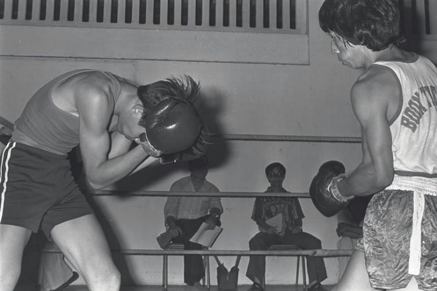 The power and drive of Tan Cheng Joo (right) proved too much for Chia Soon Gin, who preferred to stay low and away from the thundering blows in the flyweight bout of the Singapore Amateur Boxing Association's final trial at the Farrer Park gymnasium