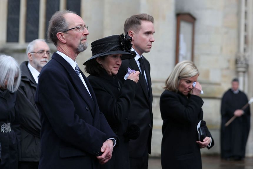 Jane Hawking (centre), first wife of Stephen Hawking, his son Tim (second right) and daughter Lucy Hawking, gesture as they watch the coffin.