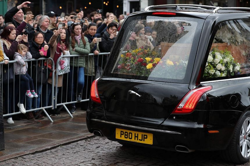 Well-wishers look at the coffin of British scientist Stephen Hawking inside the hearse after the funeral service.