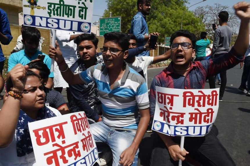 Members of the National Students Union of India hold placards as they shout slogans during a protest against Education Minister Prakash Javadekar in New Delhi on March 30, 2018.