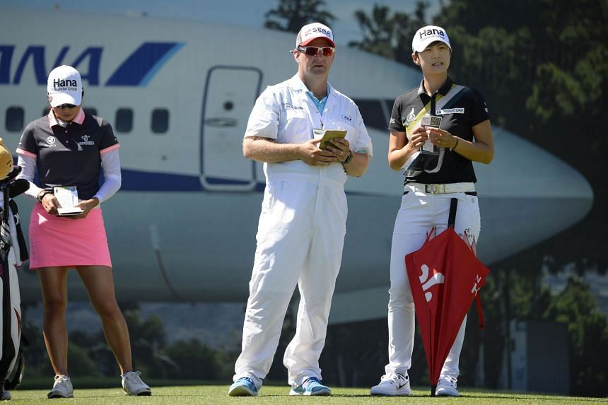 Park talks to her caddie on the 17th tee box as Minjee Lee of South Korea looks at her yardage book during round two.