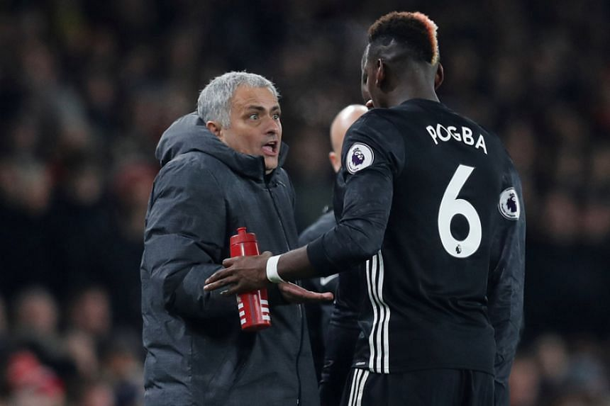 Manchester United's Paul Pogba speaks with manager Jose Mourinho during the English Premier League match against Arsenal on Dec 2, 2017.