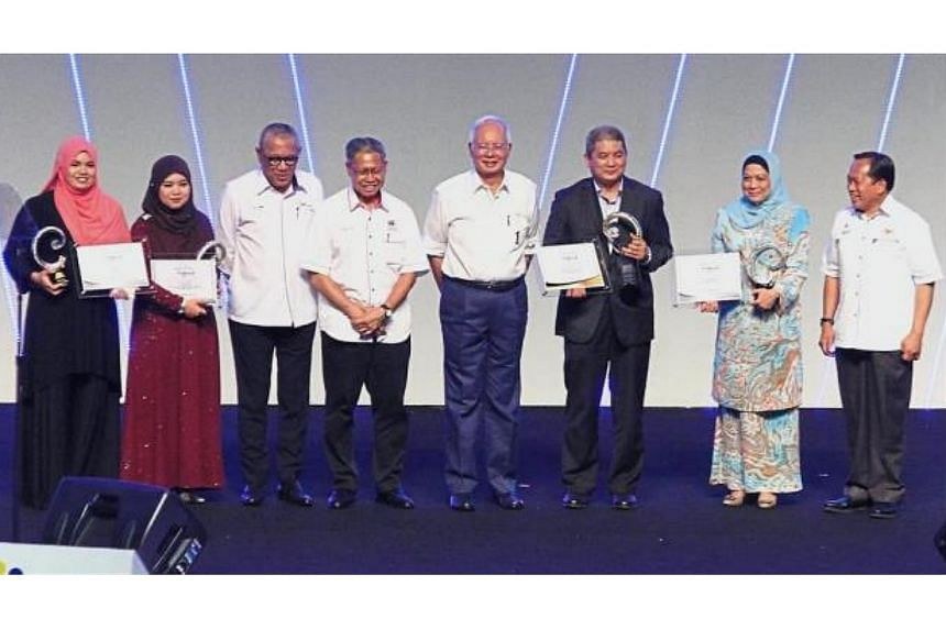 Malaysian Prime Minister Najib Razak pose with the recipients of the Bumiputera Entrepreneur awards, SME Corp Chairman Tan Sri Mohd Al-Amin Abdul Majid (third from left), Minister of International Trade and Industry Datuk Seri Mustapa Mohamed (fourth