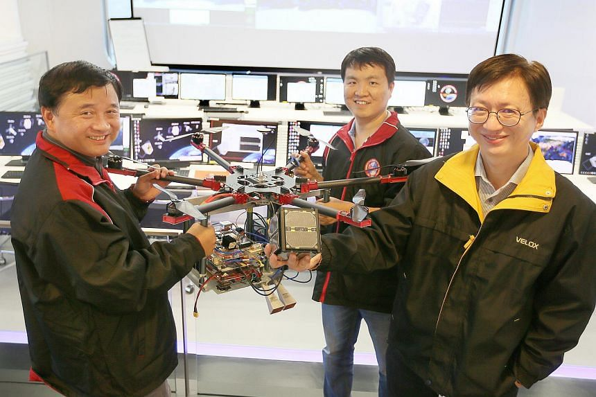 Project lead Professor Lu Yilong (left) and senior research fellow Liu Weixian (centre) carry the drone carrying the prototype of the synthetic aperture radar, while NTU Satellite Research Centre director Lim Wee Seng holds a microsatellite that the