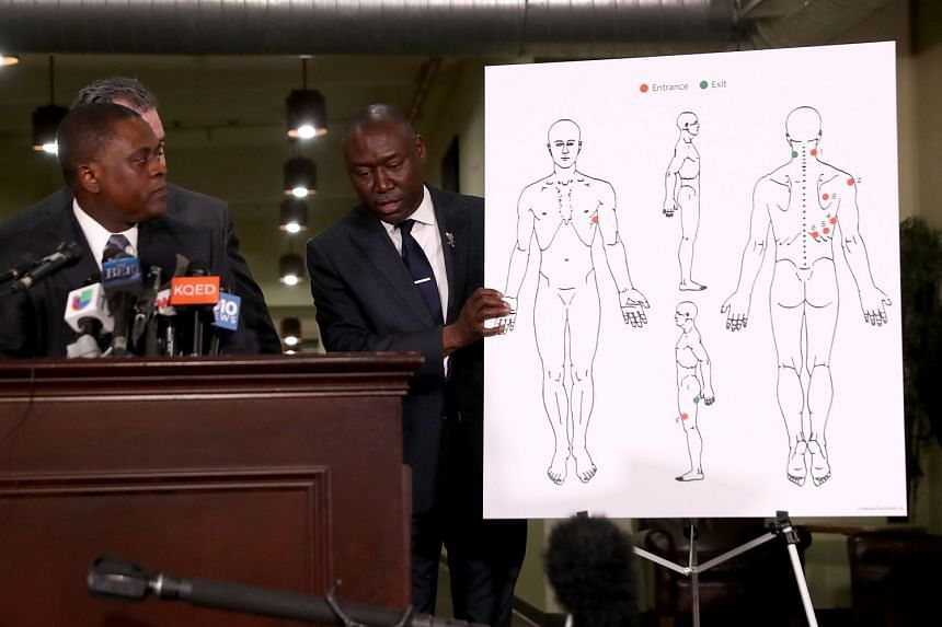Attorney Ben Crump holds a diagram showing gunshot wounds inflicted on Stephon Clark during a news conference at the Southside Christian Center, on March 30, 2018.