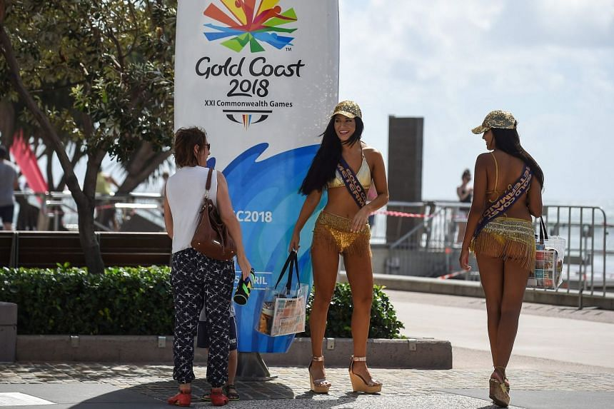 """""""Meter maids"""" walk past signage for the 2018 Gold Coast Commonwealth Games on March 31, 2018."""