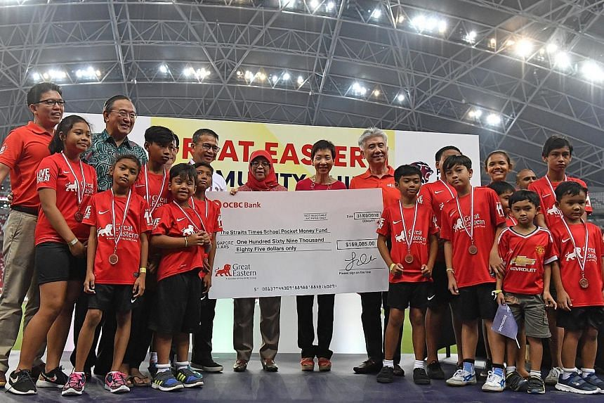 President Halimah Yacob, Minister for Culture, Community and Youth Grace Fu, FAS vice-president Edwin Tong (in white), Great Eastern Holdings group chief executive Khor Hock Seng and Charity Council chairman Gerard Ee (in green) on stage with a chequ