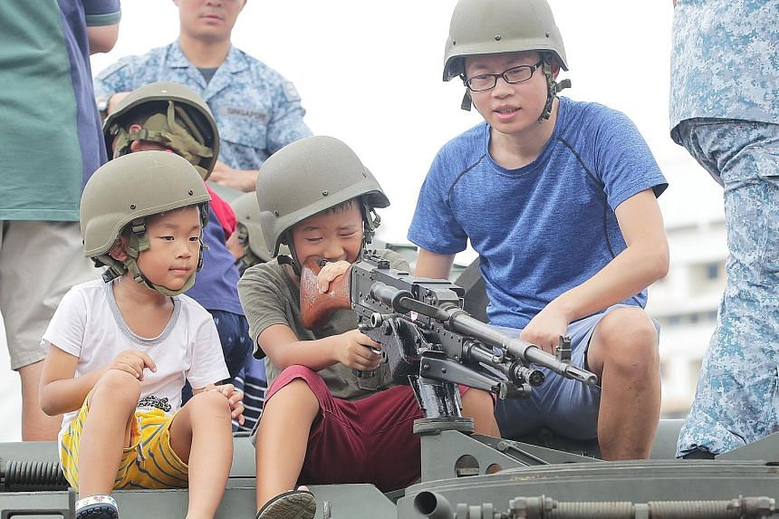 """Visitors taking part in interactive activities at the exhibition. The event also featured a naval helicopter simulator as well as different aircraft displays. RSAF medical officers carrying a """"casualty"""" on a stretcher to a Super Puma that had landed"""