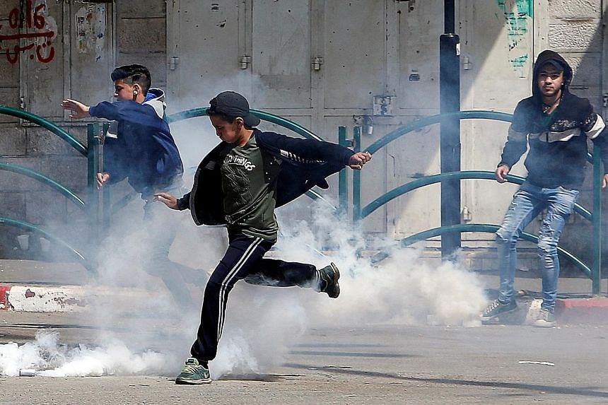 A Palestinian kicking a tear gas canister fired by Israeli troops during clashes in Hebron, in the West Bank, yesterday. Israeli troops fired warning shots towards Palestinian youths gathered at the Gaza-Israel border, wounding 13 people, a day after