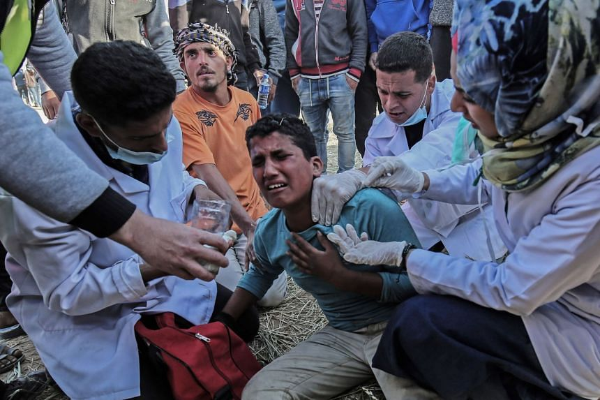 Medical staff help an injured Palestinian man during clashes with Israeli security forces on March 31, 2018.