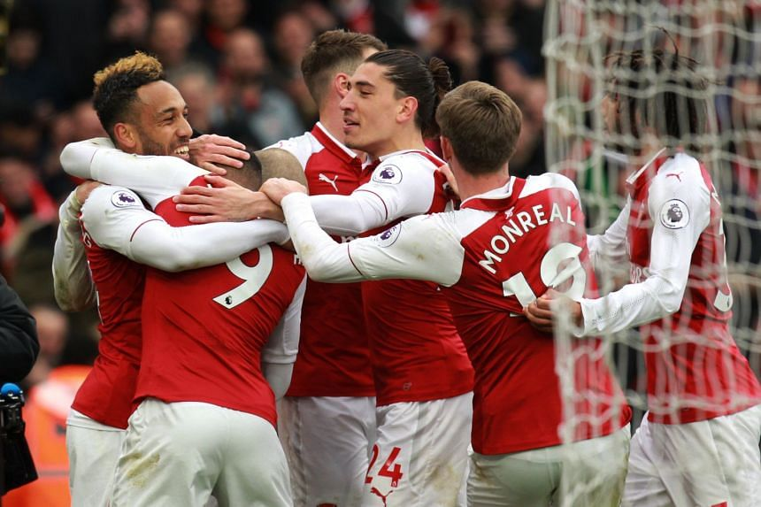 Arsenal striker Pierre-Emerick Aubameyang (left) celebrating with teammates after scoring against Stoke City during their EPL match on April 1, 2018.